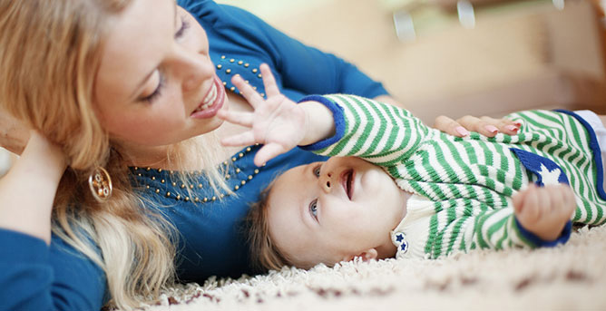 Mother and toddler lying on carpeted floor. Toddler is smiling and reaching up at the mother.